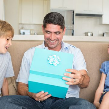 Happy father opening gift given by children on sofa at home