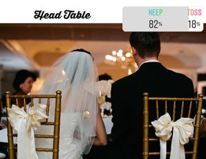 bride and groom sitting at head table gold chiavari chairs white satin bows
