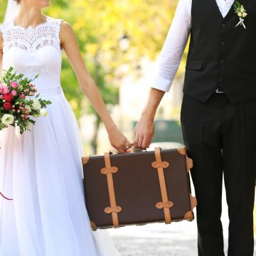 Groom and bride with vintage suitcase walking in park