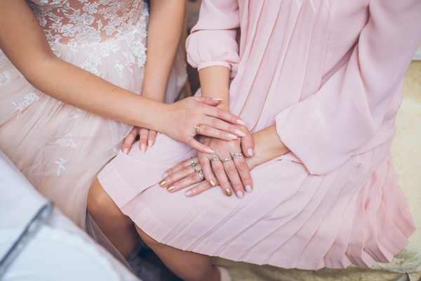 bride and mother holding hands | tips for family wedding drama