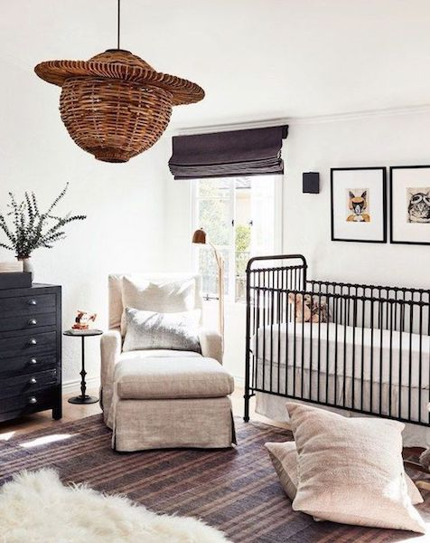 A black crib and dresser really pop in this white and cream nursery space