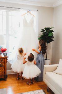 Flower girls and junior bridesmaid looking at wedding dress